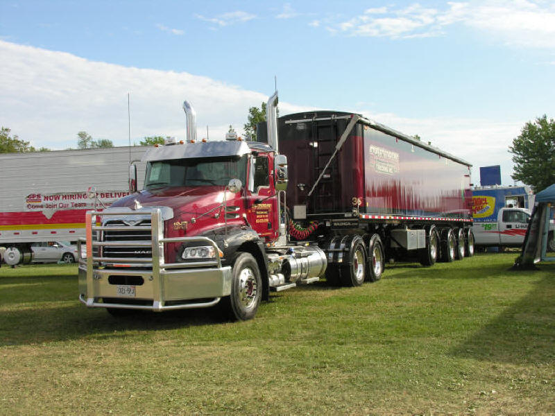 Picture of nice Red and Black Mack Truck with matching heavy duty trailer at truck show